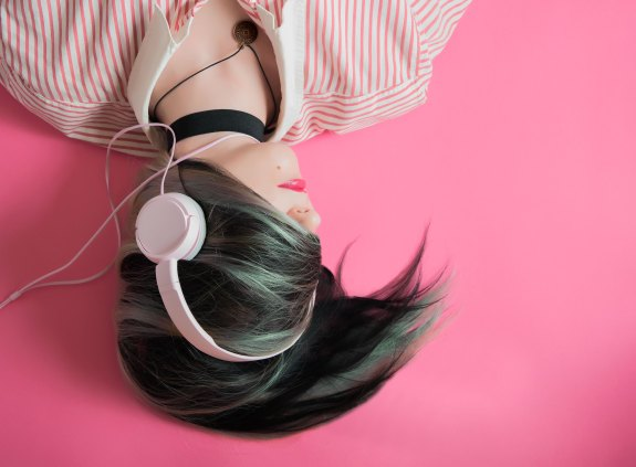 Photo of a woman wearing headphones, lying on a pink surface