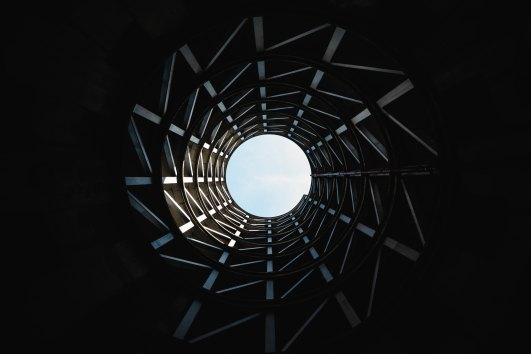 Photograph of the inside of a tower from the bottom, looking up