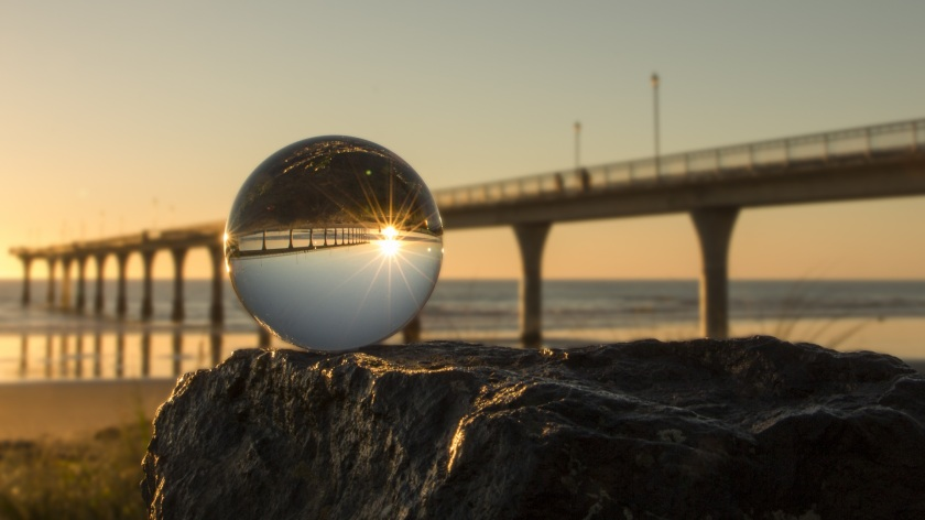 Photograph of a crystal sphere sitting on a rock by the seaside. The sunrise is captured in the heart of the sphere as a bridge extends off into the distance.