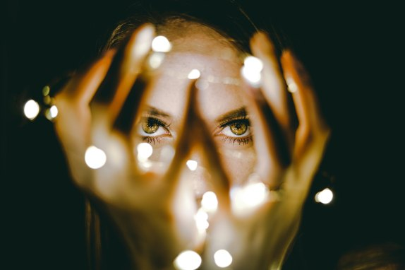 Photograph of a woman's eyes. In the foreground, her hands are held up, wrapped in lights to cast light on her face. The photographer has focused on the woman's eyes, giving them emphasis while leaving the raised hands out of focus.