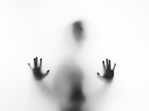 Photograph of the hazy image of a person on the far side of a white surface, hands splayed against it as though trying to push through